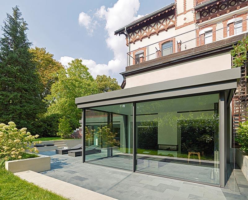 Die großen Glasflächen und der einheitliche Fußbodenbelag heben die Schwelle zwischen Innen- und Außenbereich auf. Bildnachweis: Solarlux GmbH