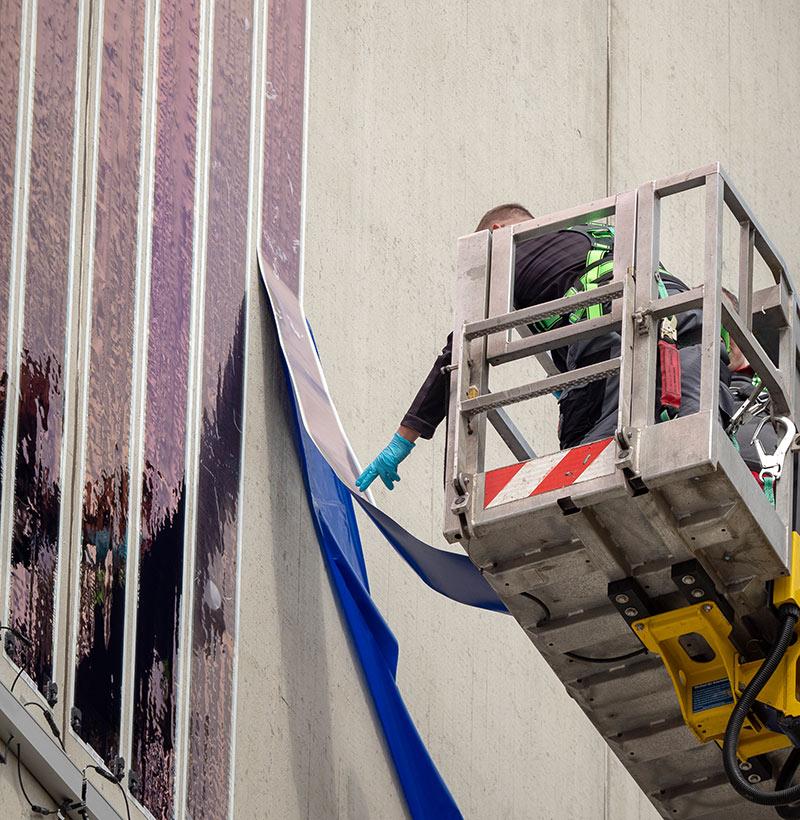 Die Solarfolie ist sehr dünn und biegsam und wird einfach auf die Fassade geklebt. Fotos: LEW / Timian Hopf