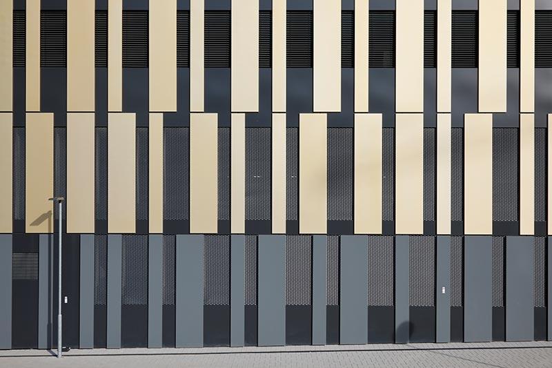 Die Herausforderung für Freyler Metallbau lag darin, die vorgehängte goldfarbene Blechfassade und die dunkle Unterkonstruktion aus Aluminium optisch und technisch einwandfrei miteinander zu verbinden. Foto: Hopermann Fotografie/FREYLER