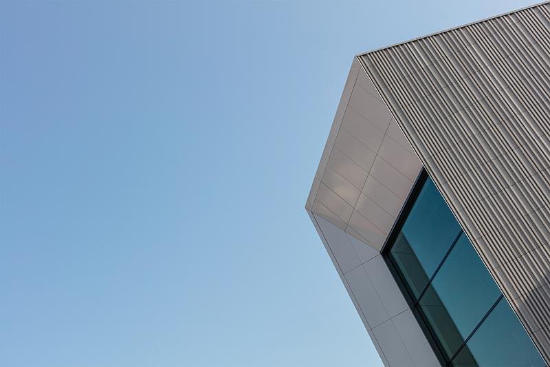 Eine Fassade, die je nach Lichteinfall und Witterung ihr Erscheinungsbild variiert. Die elegante Oberfläche färbt sich bei Niederschlag dunkler und reflektiert sanft die umgebenden Lichtstimmungen. Foto: Alexander Bernhard