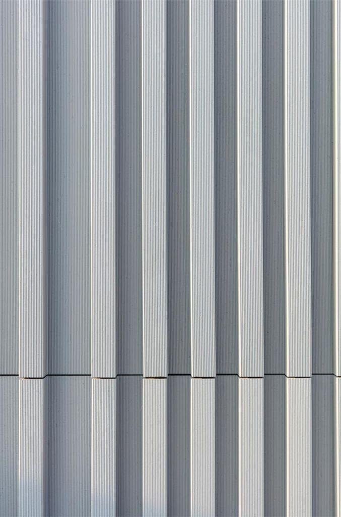 Auf Wunsch der Architekten wurde die gekämmte Oberflächenstruktur sowie die Farbgestaltung der Keramikplatten mit einer seidenmatt grauen Glasur individuell von Moeding angefertigt. Foto: Alexander Bernhard