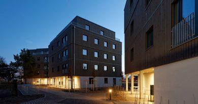 Beleuchteter Eingangsbereich: Rücksprünge in der Fassade markieren den Zugang zu den Gebäuden. Foto: Brüninghoff