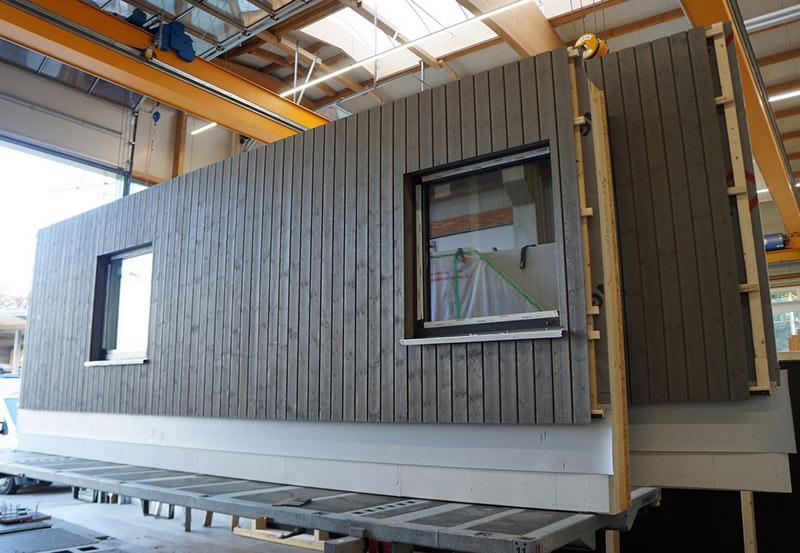 Bereits im Werk wurden die Holztafelelemente für die Fassade mit Fenstern, Dämmung, Lattung und Installation versehen, um eine schnelle Montage auf der Baustelle zu gewährleisten. Foto: Brüninghoff