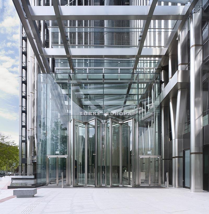 """Der gläserene Kubus fungiert als repräsentativer Eingangsbereich in den Büroturm """"Torre Europa"""". Foto: Bellapart"""