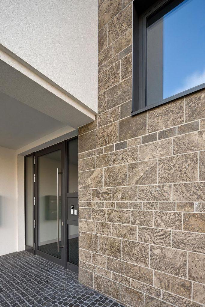 Vor allem in der Kombination mit verputzten Flächen entfaltet der direkt auf dem WDVS verklebte Naturstein sein gestalterisches Potenzial. Foto: Axel Stephan, Frankfurt/M.