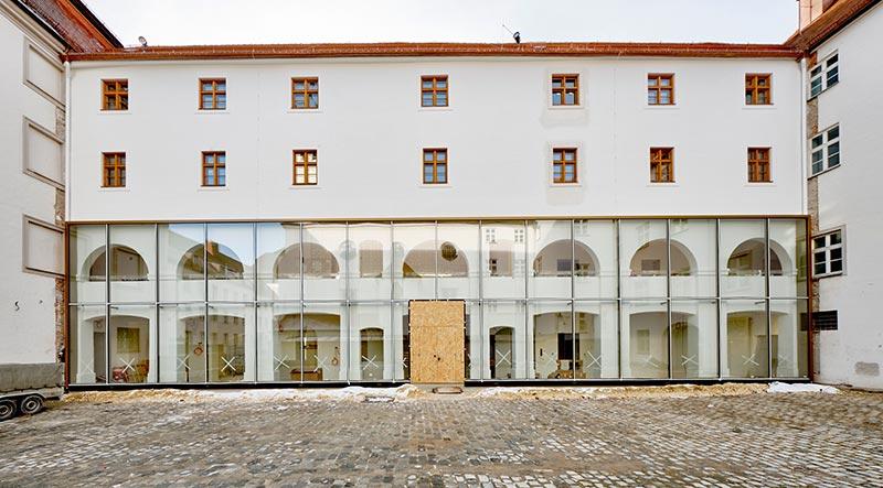 In der Glasfassade des Eingangsbereiches spiegelt sich eindrucksvoll das Sgraffito-Muster der Hofkirche. Foto: Ingo Jensen/Schwenk Putztechnik