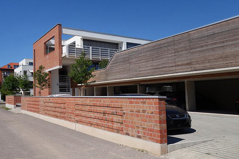 Durch den Carport ist ein winkelförmiger Gebäudekomplex mit geschütztem Gartenbereich entstanden. Auf dem Carport ließ die Baugemeinschaft einen Gemeinschaftsbereich errichten. Foto: Markus Eichhorn