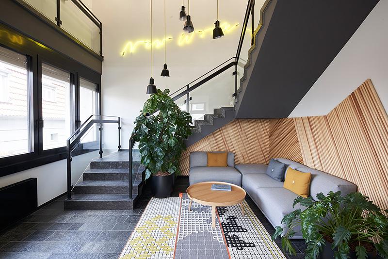 Die Wandverkleidungen der Büro- und Besprechungsräume bestehen aus schnell nachwachsenden Seekieferplatten und die angefertigten Sondermöbel sind ebenfalls nachhaltig zertifiziert. Foto: Schüco International KG