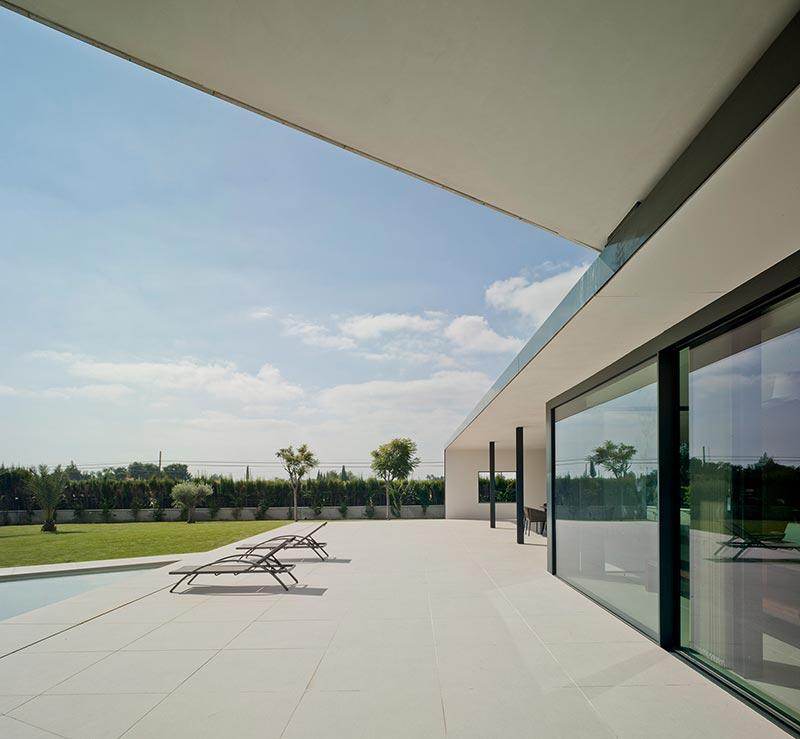 Für den Außen- wie Innenbereich wurde helles Natursteinzeug für die Böden eingesetzt, um eine optisch überganslose, einheitliche Bodenfläche zu erhalten. Bildnachweis: Schüco International KG / David Frutos