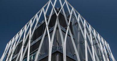 Die dünnen, weißen Aluminiumstreben ranken sich rund um das Gebäude und erstrecken sich bis über das oberste Stockwerk hinauf.