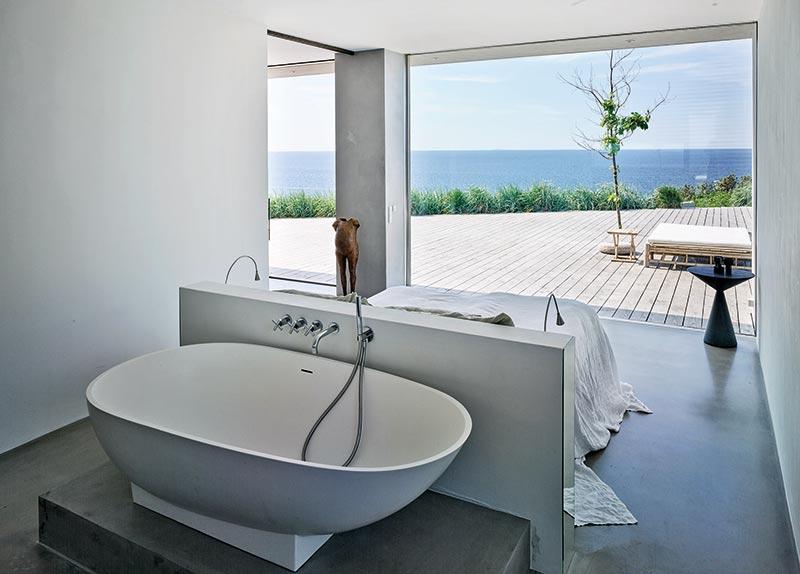 Auch das Schlafzimmer mit Badewanne ist offen gestaltet und lenkt den Blick nach draußen. Foto: Kirstine Mengel