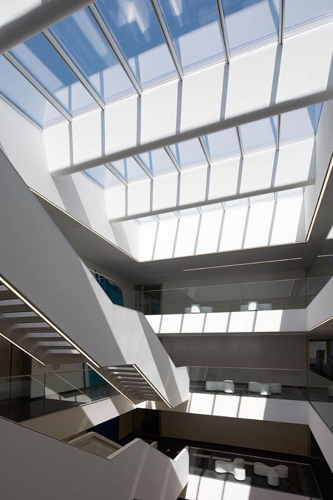 Das Atrium-Lichtband aus Velux Modular Skylights im Hauptgebäude lässt das Tageslicht auch tief ins Gebäudeinnere fallen. Durch wechselnde Tageszeiten und Wetter ergibt sich ein faszinierendes Spiel von Licht und Schatten. Fotos: Velux / Jesper Blaesild