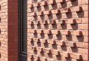Die aus der Fassade heraustretenden Köpfe brechen die Fassade auf und erzeugen eine gewisse Dynamik im Fassadenbild. Bild: Simon Schnepp, Fotografie
