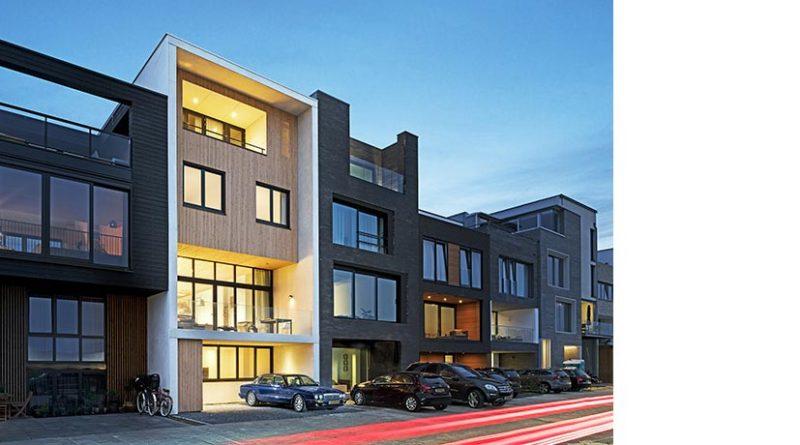 Das schmale Reihenhaus in Ijburg grenzt sich bereits mit der Fassade aus weißem Betonumbau und Holz von den anderen Gebäuden Bildnachweis: Solarlux GmbH