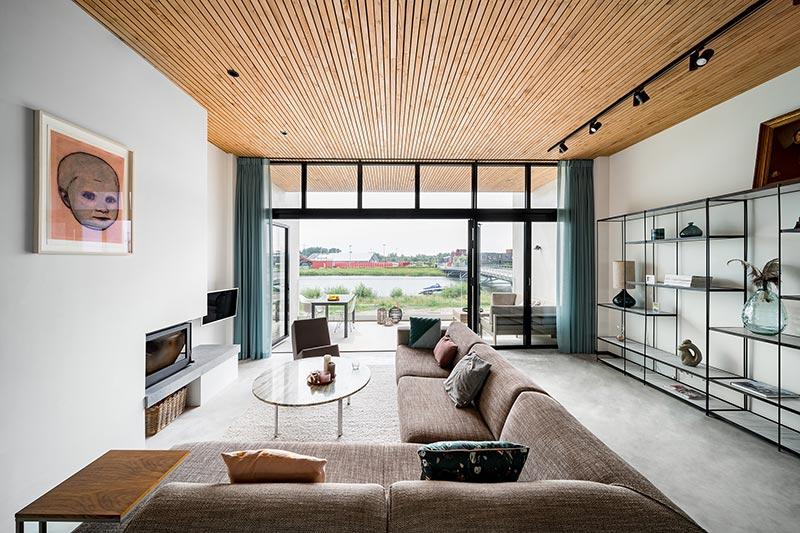 Die Glas-Faltwand im Wohnzimmer verbindet den Innenraum mit der Umgebung und ermöglicht vom Sofa aus einen herrlichen Ausblick aufs Wasser. Bildnachweis: Solarlux GmbH