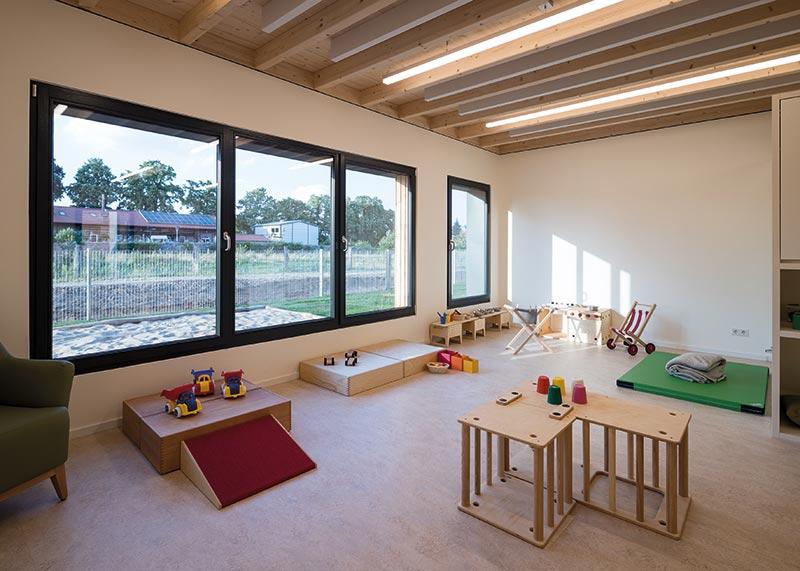 Helle Räume mit Holzbalkendecken bieten einen geschützten Raum für die Kinder. Bildnachweis: SWISS KRONO | Foto: Jan Meier