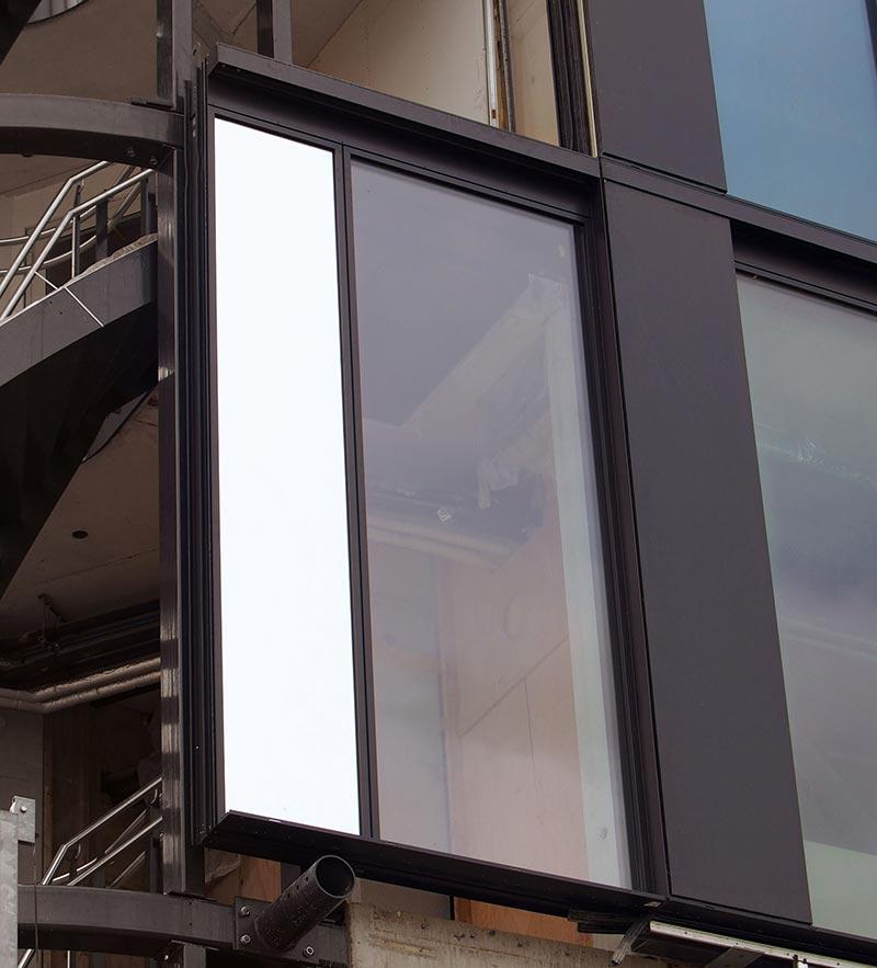 Die Fassadenelemente mit Festverglasungen aus Funktions-Isolierglas sind mit einer auf dem Standardfassadensystem HUECK Trigon Unit L basierenden Sonderlösung realisiert. Die elektronisch gesteuerten Paneele wurden nachträglich montiert. Quelle: HUECK