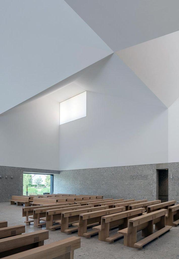 Der Innenraum ist sehr reduziert mit Stein im unteren und Kalkputz im oberen Bereich ausgeführt. Die Bänke, die bis zu 350 Besuchern Platz bieten, orientieren sich um den Altar. Foto: Florian Holzherr
